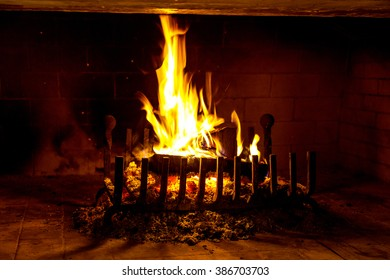 Traditional fireplace with burning firewood and charcoal in modern interior. Beautiful view of fire in fireplace create warm and cozy picture. As background for design