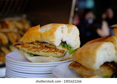 Traditional fish sandwich served on the dock of Eminonu area of Istanbul.  Sandwich is main focus with grill and sit down area off focus in back