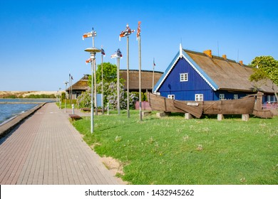 Traditional fishermen's house with old wooden viking boat and traditional wooden symbols in Nida, Lithuania, Europe. Curonian Spit between the Curonian Lagoon and the Baltic Sea. Unesco Heritage
