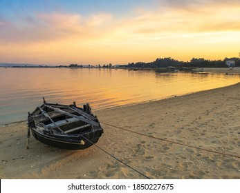Barco de pesca tradicional anclado en la playa de Riason en la isla de Arousa al atardecer dorado