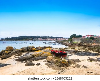 Traditional fishing boat on Abilleira beach whith Arousa island village at background