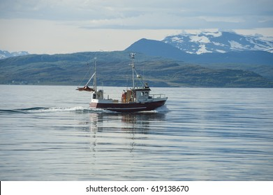 Traditional fishing boat on sea at speed with mountains in background