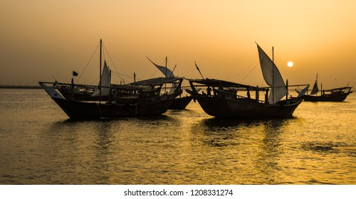 Traditional fishing boats, dhows, come to rest in the harbor below the gold of the setting sun , Dammam, Eastern Province, Saudi Arabia