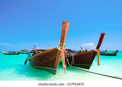 Traditional fishing boats floating over an exotic clear sea and beach of island in Andaman sea, Southern Thailand
