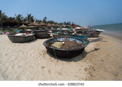 Traditional fishing boats on the beach of Hoi An city, the cityscape and Son Tra peninsulain are visible in distance. Vietnam.