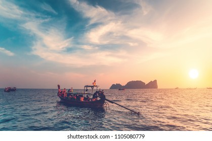 The traditional fishing boats with the tourists in the ocean next to the exotic Phi Phi Islands, the Kingdom of Thailand. Breathtaking colorful sunset background. Beauty of wild nature.
