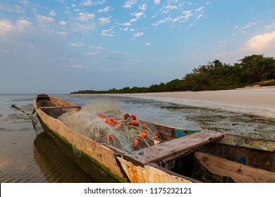 Traditional fishing canoe at the beach in the island of Orango at sunset, in Guinea Bissau. Orango is part of the Bijagos Archipelago; Concept for travel in Africa and summer vacations