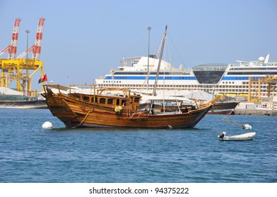 A traditional fishing dhow is anchored in Muscat Harbor, Oman. Cruise ship  is in background.