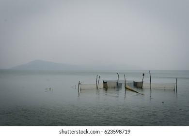 Traditional fishing nets installation in calm ocean fog.