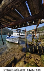 Traditional fishing oats in Limski kanal (canal), Croatia, seen from under the wooden pier.