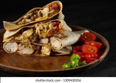 Traditional flatbread quesadillas with chicken, cheese and vegetables salsa. Black background for copy text menu recipe.