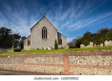 Traditional flint walled medieval English village church and graveyard or churchyard at Sparsholt near Winchester in Hampshire England UK with blue skies and clouds in summer