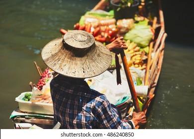 Traditional floating market Damnoen Saduak in Ratchaburi near Bangkok, Thailand. - selective focus on the old wicker hat