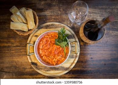 Traditional Florentine tripe in a bowl with a Chianti glass on a side and olive oil focaccia