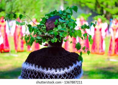A traditional folk culture. The colorful summer outdoor feast. The womam with wreath look at the folk ensemble