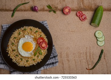 traditional food, egg fried rice with vegetable cuts, tomatoes, cucumber, chili, and empty space