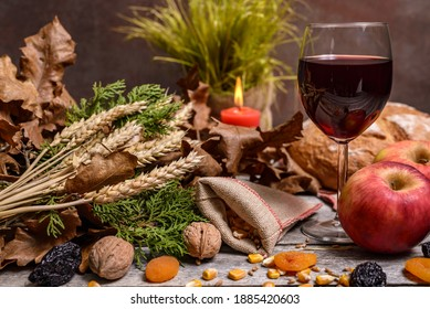 Traditional food for orthodox Christmas eve. Yule log or badnjak, wine, bread, apples, cereals, dried fruits and burning candle on rustic table. Concept celebration orthodox Christmas.