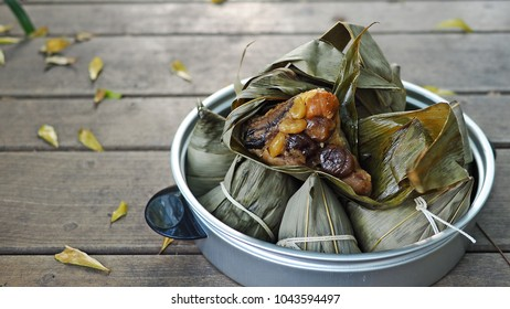 Traditional food zongzi or rice dumpling for Dragon Boat Festival. Zongzi in vintage aluminium steamer or steaming pot on wooden background. (close up, selective focus, space for text)