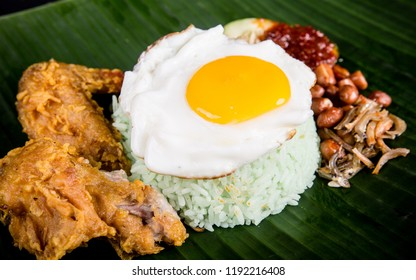 Traditional fragrant coconut rice served with fried egg, deep fried chicken wings and sambal chilli on top of a banana leaf. Nasi Lemak from Singapore.