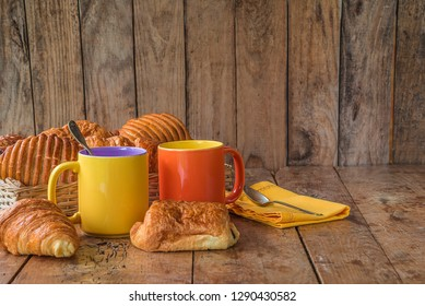 Traditional french breakfast with hot coffee and croissants: two mug of coffee, wicker basket with hot croissants and yellow napkin on vintage wooden background with copy space