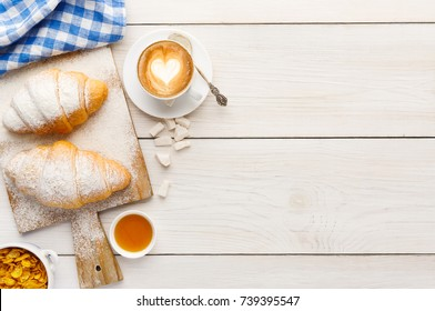 Traditional french breakfast menu background. Fresh croissants with icing, cup of coffee, muesli and honey on wooden table, top view, copy space