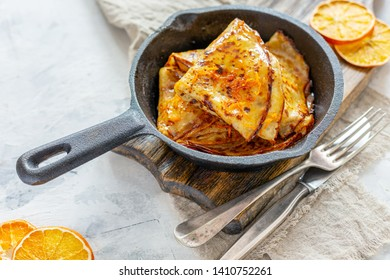 Traditional French crepe Suzette with orange sauce in a cast iron pan, selective focus.