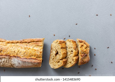 Traditional French crispy fresh baguette with a golden crust or a long loaf baked in a bakery or homemade and cut into slices, flax seeds on a gray concrete background.