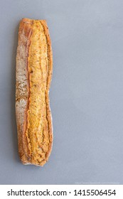 Traditional French crispy fresh whole grain bread baguette with golden crust baked from organic flour in a bakery or home made on a gray concrete background.