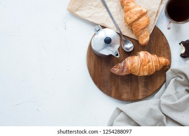 Traditional French croissant on light gray background with coffee. Tasty breakfast with croissants.Fresh bakery.Top view.