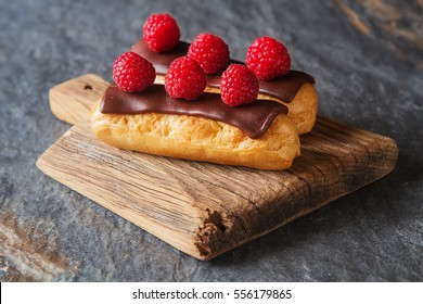 Traditional French dessert. Eclair with chocolate icing and raspberries. Dark background