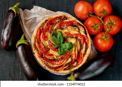 Traditional French dish quiche with vegetables and cheese on the black background. Vegetarian tart decorated with fresh eggplants, tomatoes and basil leaves. Top view