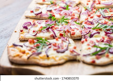 Traditional French dish tarte flambee cream cheese, bacon and onions. Flammkuchen from Alsace region. Flame cake.