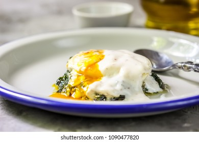 traditional French dish-Florentine eggs for Breakfast with pureed spinach on the concrete background