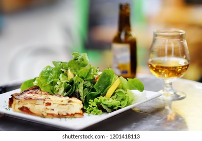 Traditional French food: quiche lorraine and fresh salad leaves with glass of beer. Healthy meal. Lunch or dinner with organic vegetables in . Typical European local farmer market