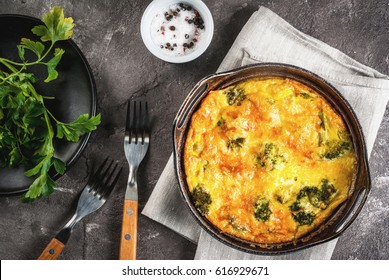 Traditional French food. quiche lorraine. Frittata. Baked in the oven egg omelet with vegetables - broccoli - cheese and greens. Rustic, homemade meal. On a gray concrete table