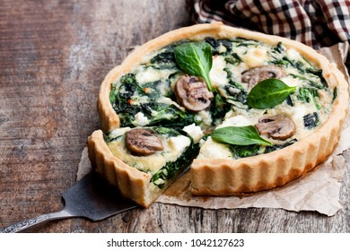 Traditional  french quiche pie with spinach and mushroom on wooden table