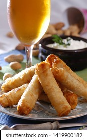 Traditional fried pastries, sigara boregi,  from Turkey, glass of cold beer and peanuts on background, selective focus