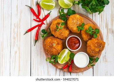 Traditional fried Spanish croquetas (croquettes) with shrimp, mint and chilly, ketchup and mayonaise on wooden background.  Fast food concept.