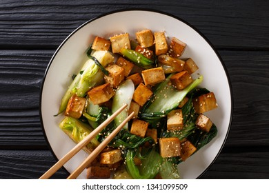 Traditional fried tofu with bok choy, soy sauce and sesame close-up on a plate on the table. horizontal top view from above