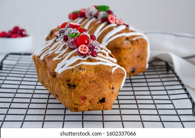 Traditional fruit cake with mixed fruit and cherries decorated with sugar icing, cranberries, pomegranate and cherry on a metal wire rack on a white background. Horizontal orientation. Close up.