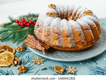 Traditional fruitcake for Christmas decorated with powdered sugar and nuts, raisins. Delicioius Homemade Pastry. New year and Christmas celebration concept
