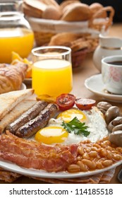 Traditional Full English Breakfast - fried sunny-side-up eggs, sausages, beans, mushrooms and bacon