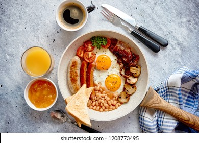 Traditional Full English Breakfast including sausages, grilled tomatoes, mushrooms, eggs, bacon, baked beans and bread. Coffee and orange juice on sides. Top view.
