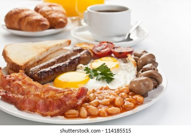 Traditional Full English Breakfast - sunny-side-up fried eggs, sausages, beans, mushrooms and bacon