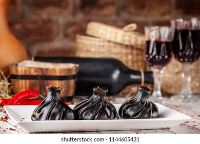Traditional Georgian and Armenian cuisine. Trend, Georgian black khinkali with meat and suluguni cheese, on a wooden table in a restaurant. Wine on the table. Copy space, selective focus
