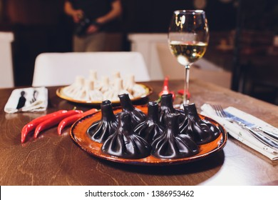 Traditional Georgian and Armenian cuisine. Trend, Georgian black khinkali with meat and suluguni cheese, on a wooden table in a restaurant. Wine on the table. Copy space, selective focus.