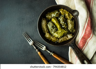 Traditional georgian dolma in grape leaves on rustic wooden table with copyspace