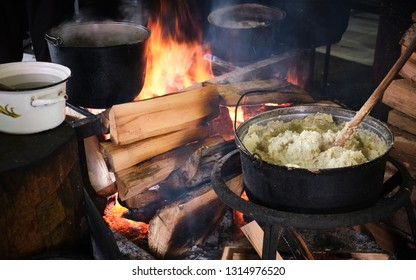 Traditional georgian food, hominy (mamaliga) is cooked in the large cooking pot on fire