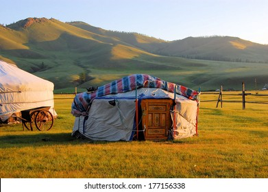 Traditional ger tent home of Mongolian nomads on the grass plains of the steppe with colorful rolling hills