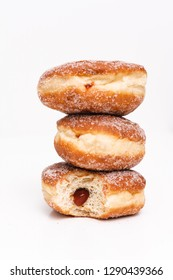 Traditional German or Austrian fried donuts with no hole, so called Krapfen, Berliner or Pfannkuchen with cinnamon sugar and filled with rose hip, raspberry or strawberry jam, party or carnival food